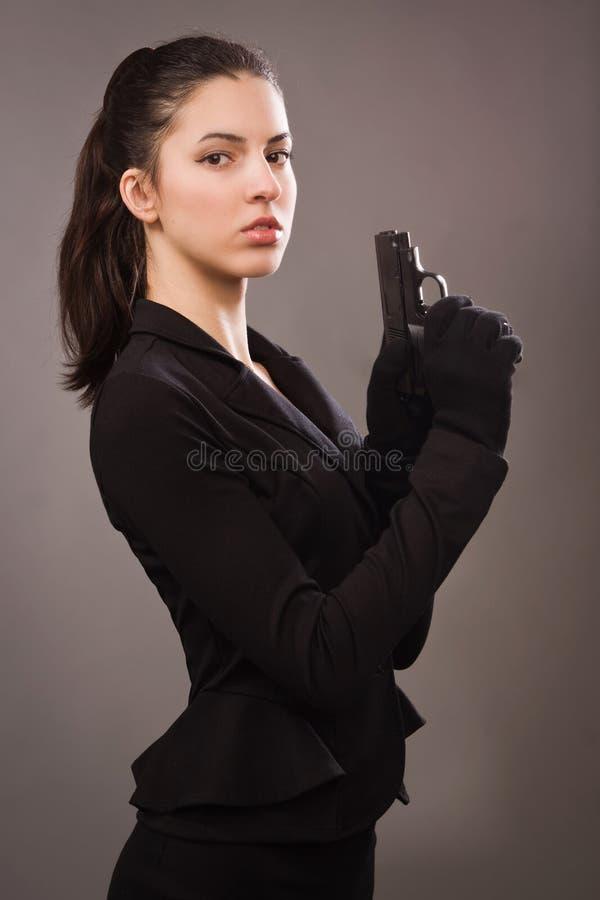 Menina do espião em um preto com arma fotografia de stock