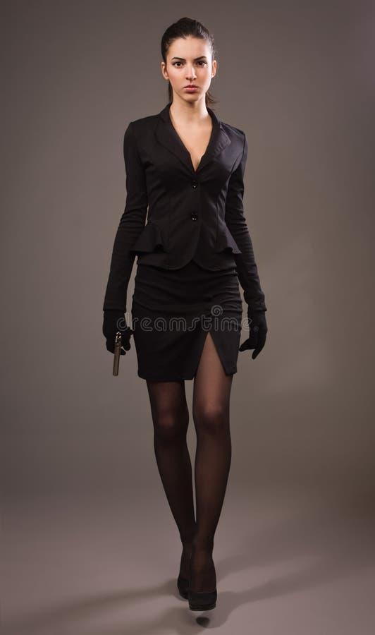 Menina do espião em um preto com arma fotografia de stock royalty free