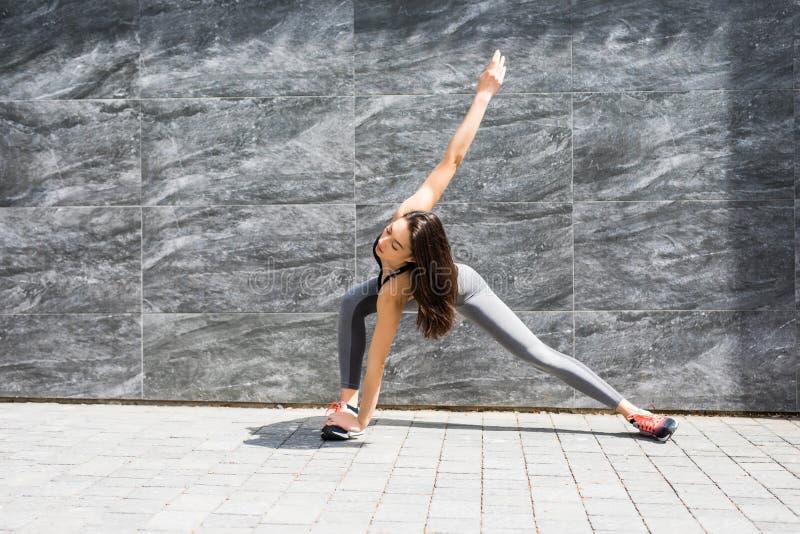 Menina do esporte da aptidão no sportswear da forma que faz o exercício da aptidão da ioga fotografia de stock royalty free