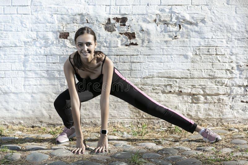 Menina do esporte da aptid?o no sportswear da forma que faz o exerc?cio na rua, esportes exteriores da aptid?o da ioga foto de stock royalty free