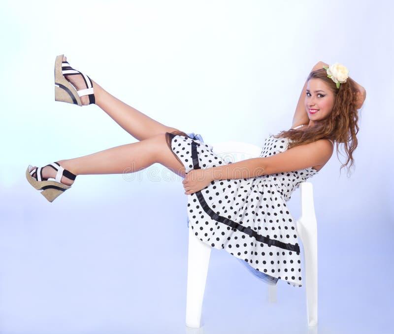 Menina do estilo Pin-acima que senta-se na cadeira foto de stock