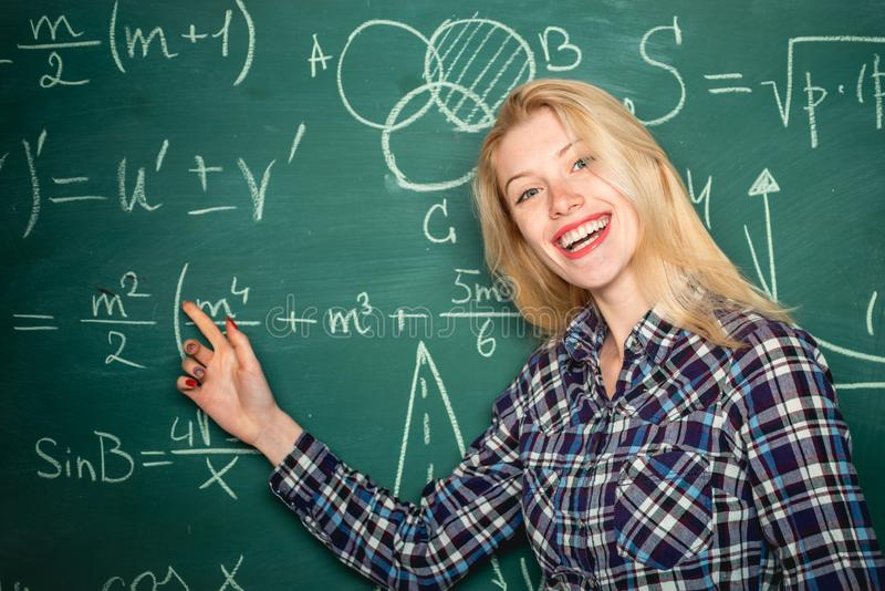 Menina do estudante com express?o feliz da cara perto da mesa com fontes de escola Estudante que prepara-se para exames da faculd fotos de stock royalty free