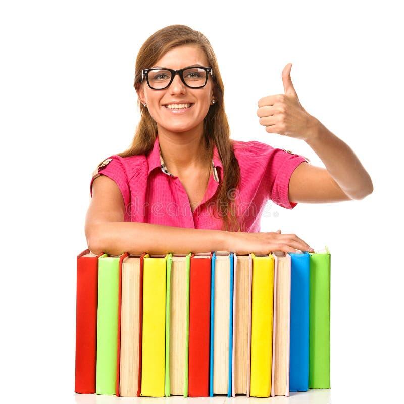 Menina do estudante com o livro da pilha que mostra o polegar acima imagens de stock