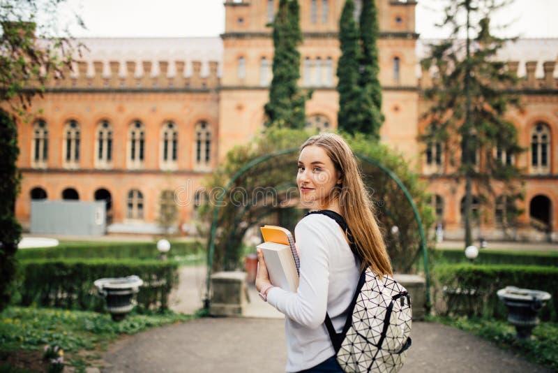 Menina do estudante com o livro em outfoors da universidade fotos de stock royalty free