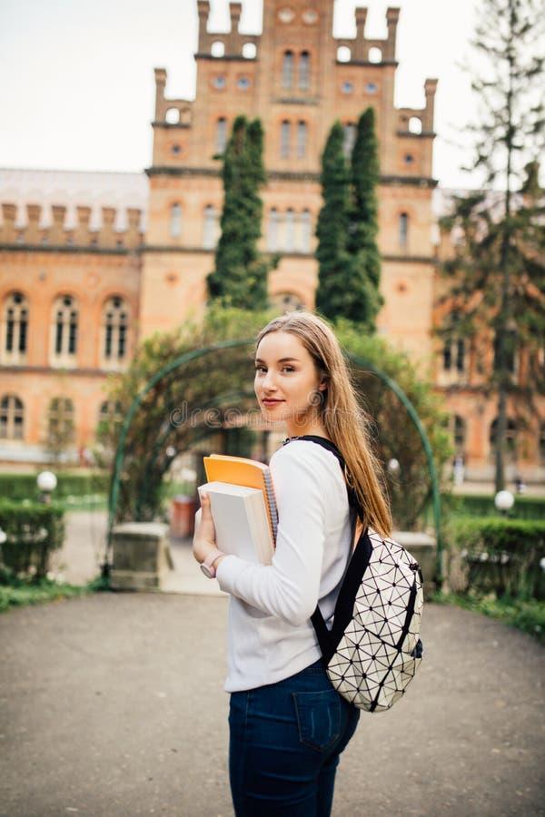 Menina do estudante com o livro em outfoors da universidade fotografia de stock