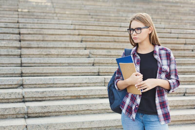 Menina do estudante com os livros no fundo de universidade imagem de stock