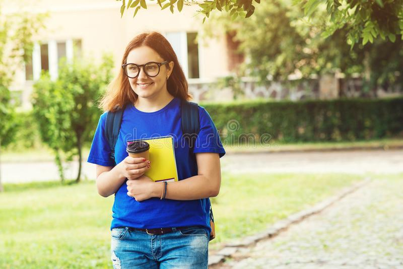Menina do estudante com a trouxa e os cadernos exteriores Menina nos vidros com takeaway do café Menina do estudante na faculdade imagens de stock