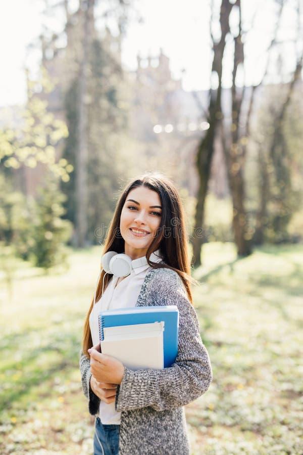 Menina do estudante de University College que olha o sorriso feliz com livro ou caderno no parque do terreno Modelo caucasiano da imagem de stock royalty free