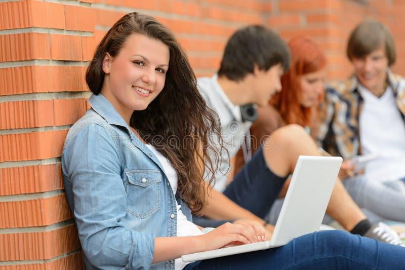 Menina do estudante fora do terreno com amigos do portátil imagem de stock royalty free
