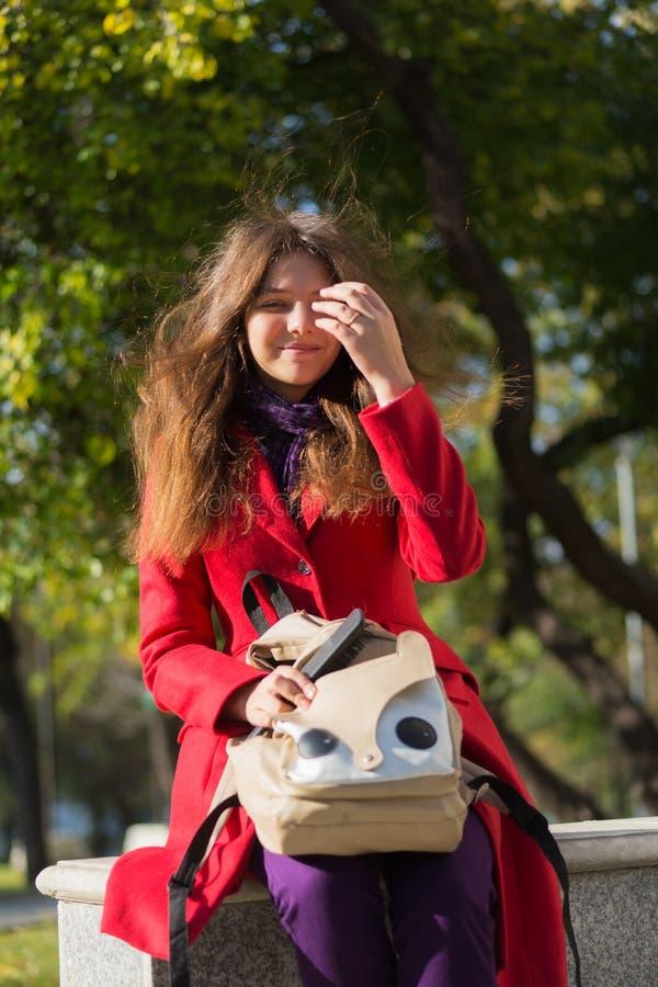 Menina do estudante fora no sorriso do parque do autunm feliz Jovem mulher m imagens de stock