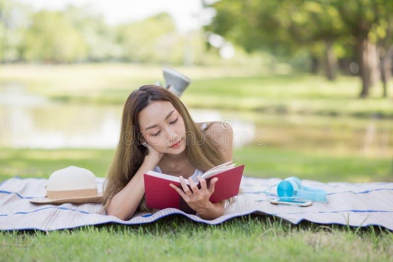 A menina do estudante leu o livro no parque imagem de stock