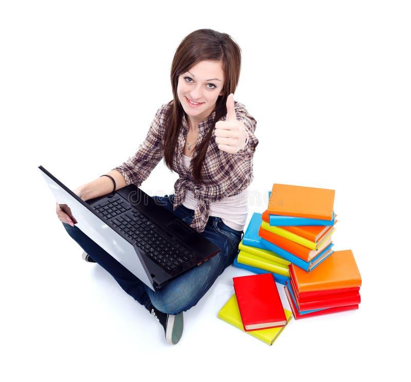 A menina do estudante mostra os polegares acima imagem de stock royalty free
