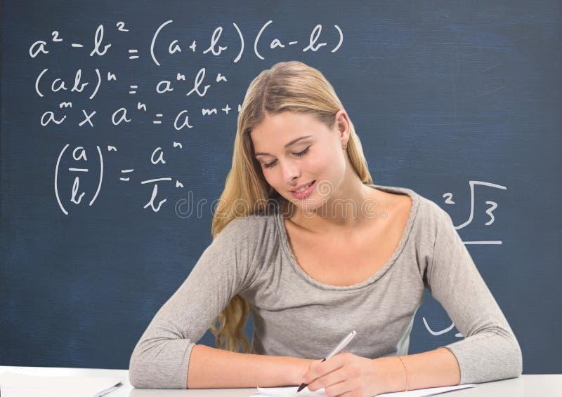Menina do estudante na escrita da tabela contra o quadro-negro azul com educação e gráficos da escola imagens de stock royalty free