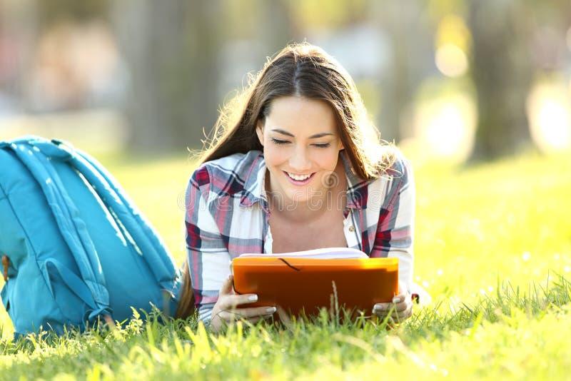 Menina do estudante que aprende notas da leitura em um terreno imagem de stock royalty free