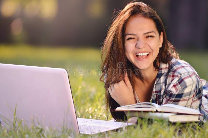 Menina do estudante que encontra-se para baixo na grama ela que trabalha no portátil e no sorriso imagens de stock