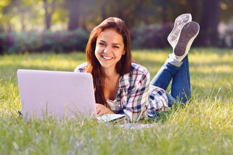 Menina do estudante que encontra-se para baixo na grama ela que trabalha no portátil e no sorriso fotos de stock royalty free