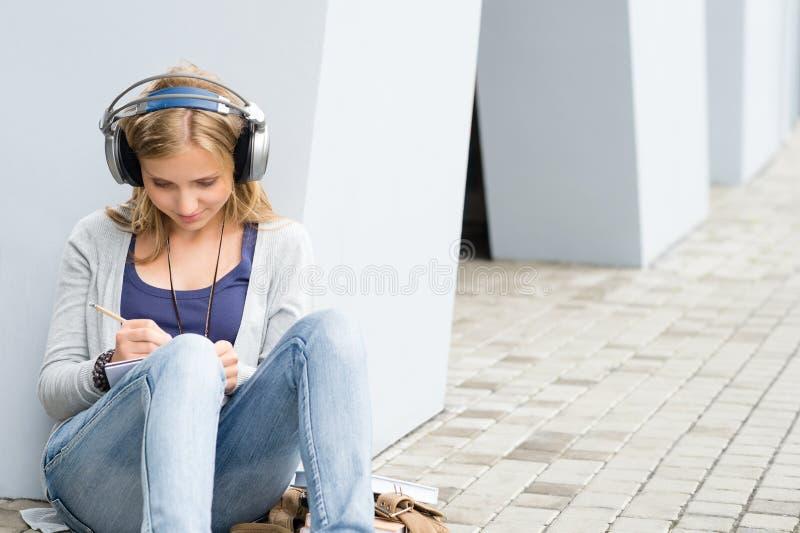 Menina do estudante que escreve e que escuta a música imagens de stock royalty free