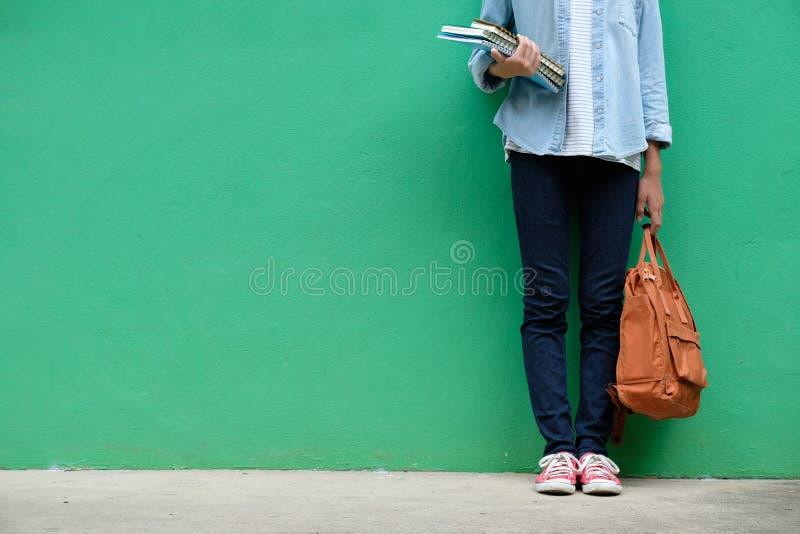 Menina do estudante que guarda livros e posição do saco de escola sobre o wa verde imagens de stock