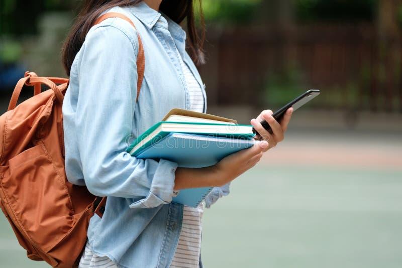 Menina do estudante que guarda livros e que usa o smartphone, educação em linha, uma comunicação da tecnologia foto de stock royalty free