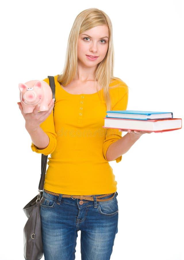 Menina do estudante que mostra livros e mealheiro foto de stock royalty free