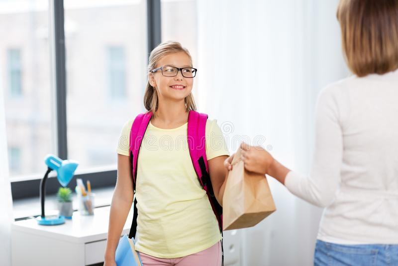 Menina do estudante que obtém o almoço escolar da mãe fotografia de stock