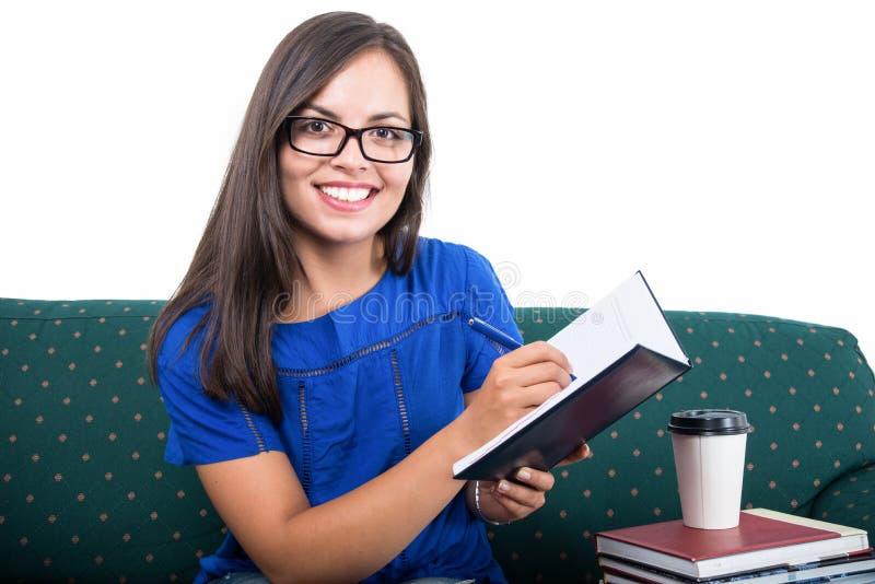 Menina do estudante que senta-se na escrita do sofá no caderno foto de stock royalty free
