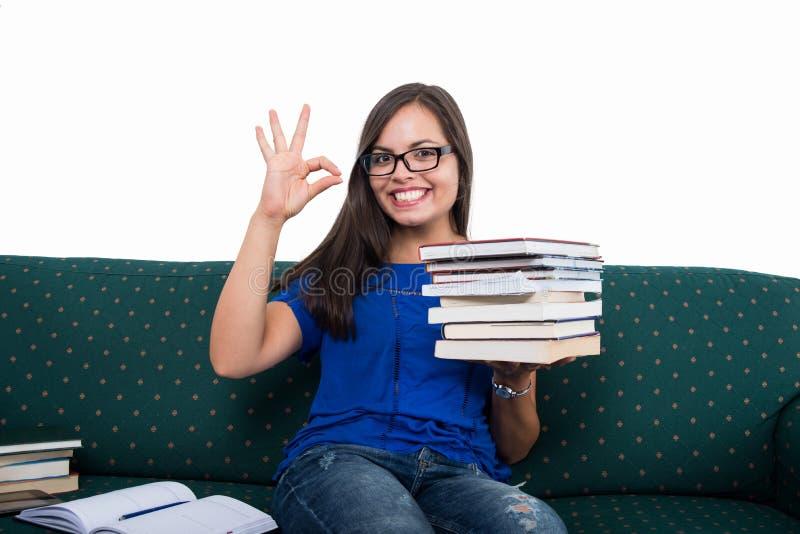 A menina do estudante que senta-se no sofá que mostra está bem guardar registra foto de stock