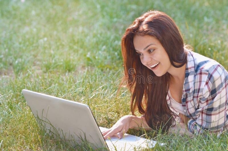 Menina do estudante que trabalha no portátil que encontra-se na grama no parque fotos de stock royalty free