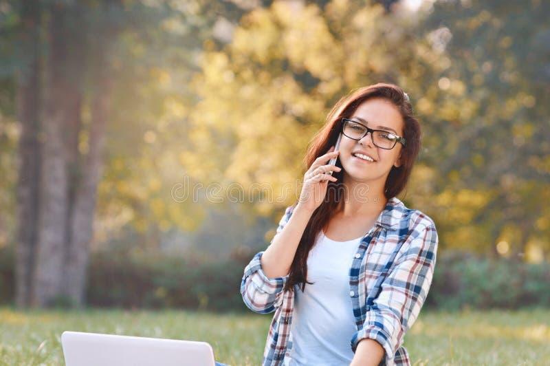 Menina do estudante que trabalha no portátil, sentando-se na grama no parque fotografia de stock