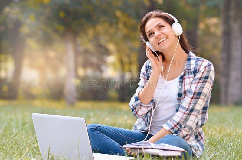 Menina do estudante que trabalha no portátil, sentando-se na grama no parque imagem de stock