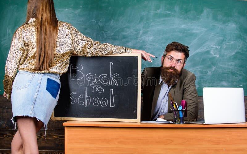 A menina do estudante seduz professor experiente O professor restrito senta o fundo do quadro da tabela Estudante na mini saia co foto de stock