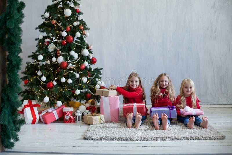 Menina do feriado três do Natal com presentes a decoração da árvore do ano novo em presentes cinzentos de um fundo imagem de stock
