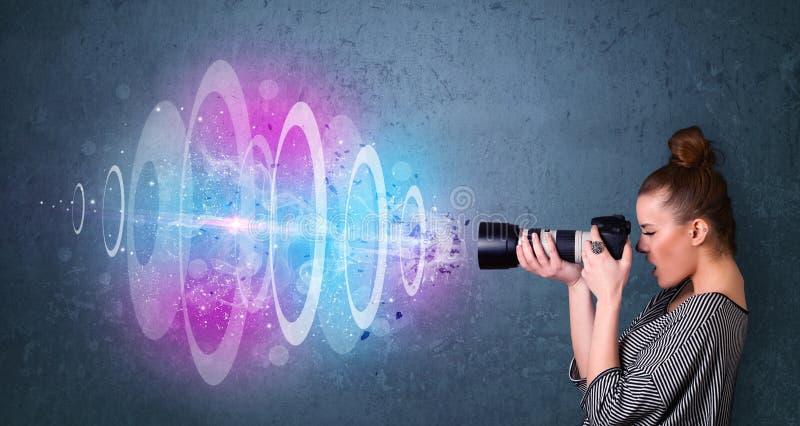 Menina do fotógrafo que faz fotos com feixe luminoso poderoso fotos de stock royalty free
