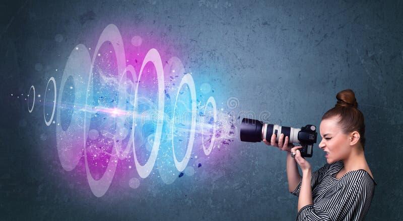 Menina do fotógrafo que faz fotos com feixe luminoso poderoso foto de stock