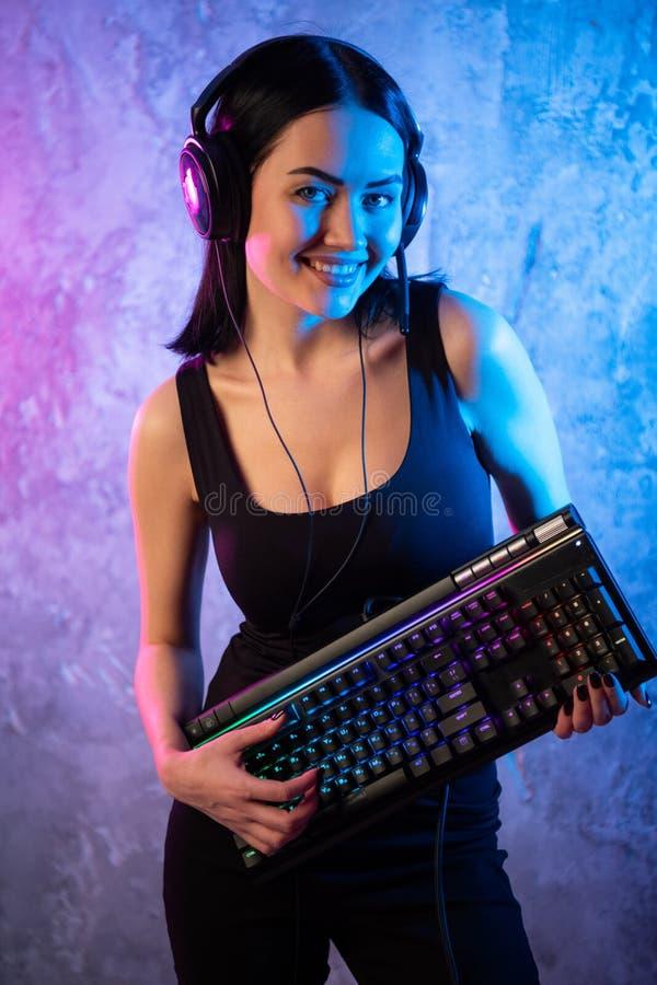 Menina do Gamer que joga com computador em casa Levantamento f?mea novo com teclado de computador imagens de stock