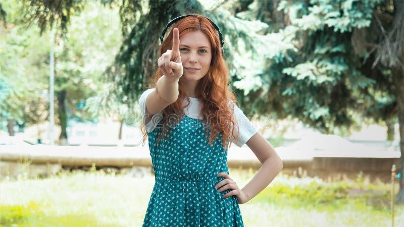 Menina do gengibre com os fones de ouvido grandes que sacodem o dedo imagem de stock royalty free