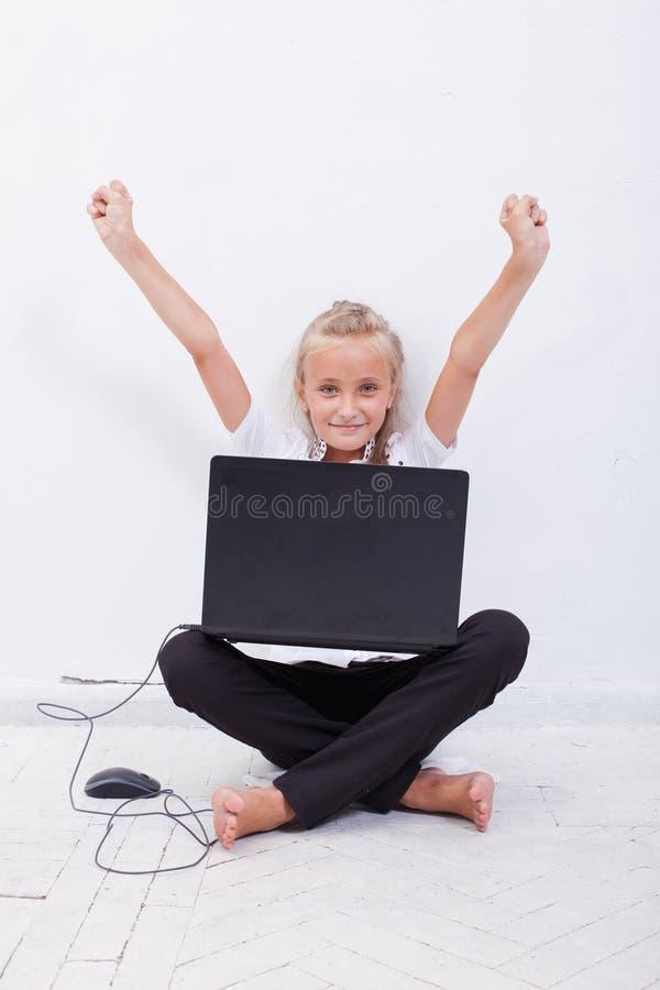 Menina do jovem adolescente com os braços aumentados usando o portátil fotografia de stock royalty free