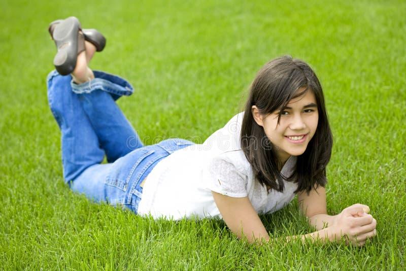 Menina do jovem adolescente que encontra-se na grama verde, relaxando imagem de stock royalty free