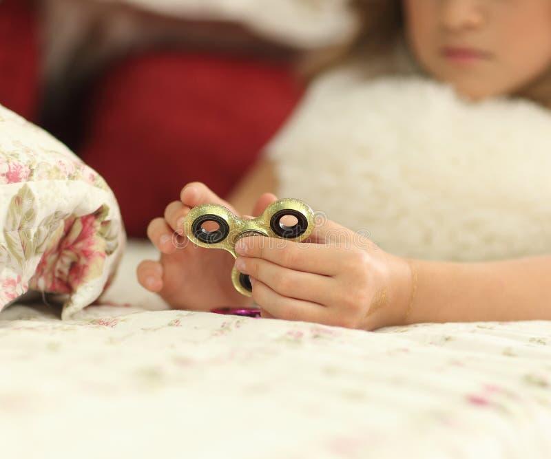 Menina do jovem adolescente que guarda o brinquedo popular do girador da inquietação - tiro do close up em casa na cama imagens de stock