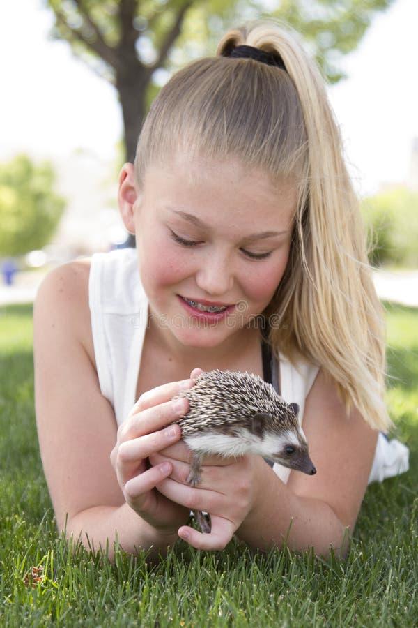 Menina do jovem adolescente que guarda um ouriço do animal de estimação fora foto de stock royalty free