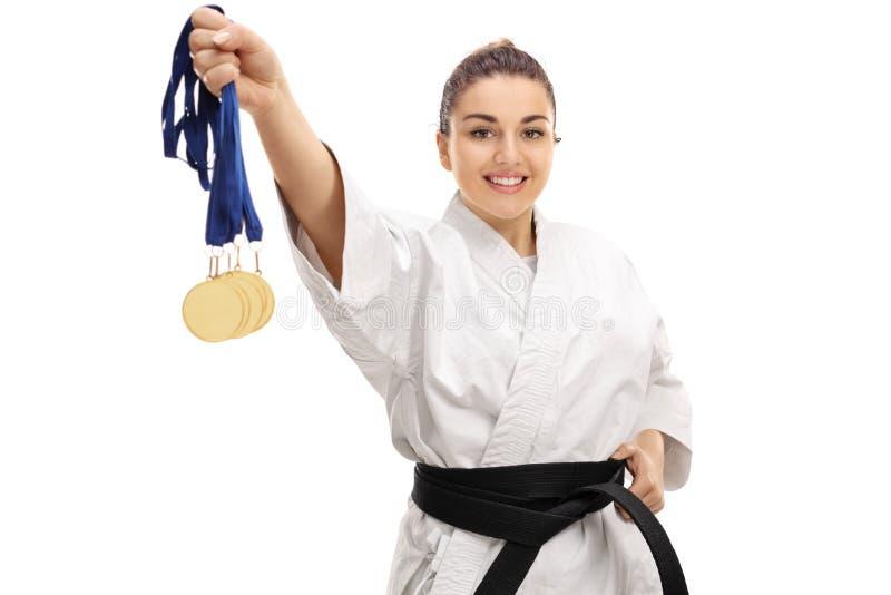 Menina do karaté que mostra medalhas e sorriso de ouro fotografia de stock royalty free