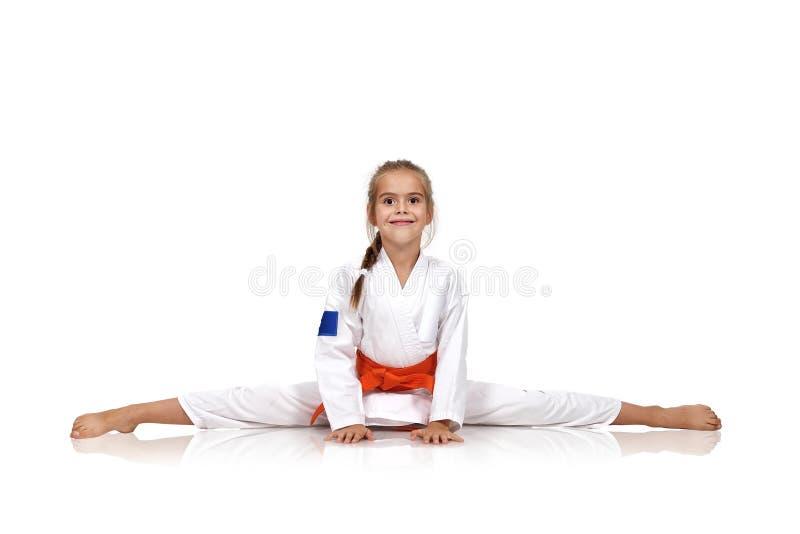 Menina do karaté que senta-se em separações imagem de stock