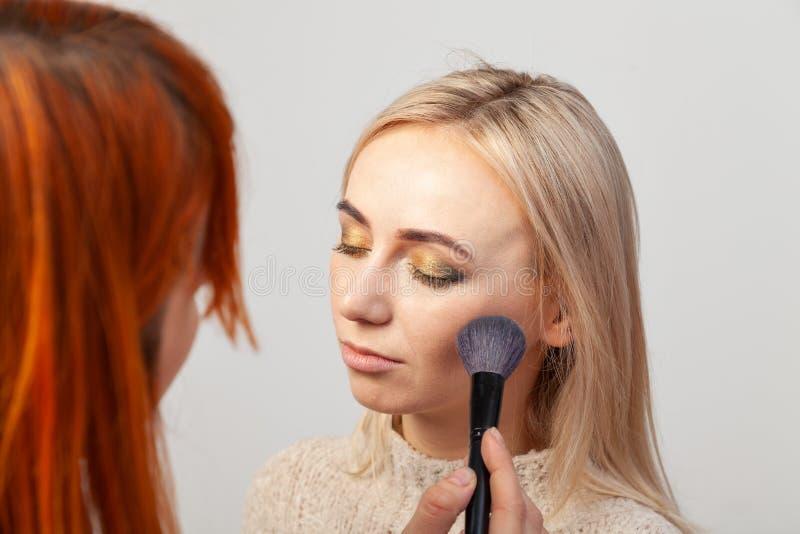 A menina do maquilhador com cabelo vermelho põe a composição sobre um modelo louro com os olhos fechados, guarda uma escova em su imagens de stock