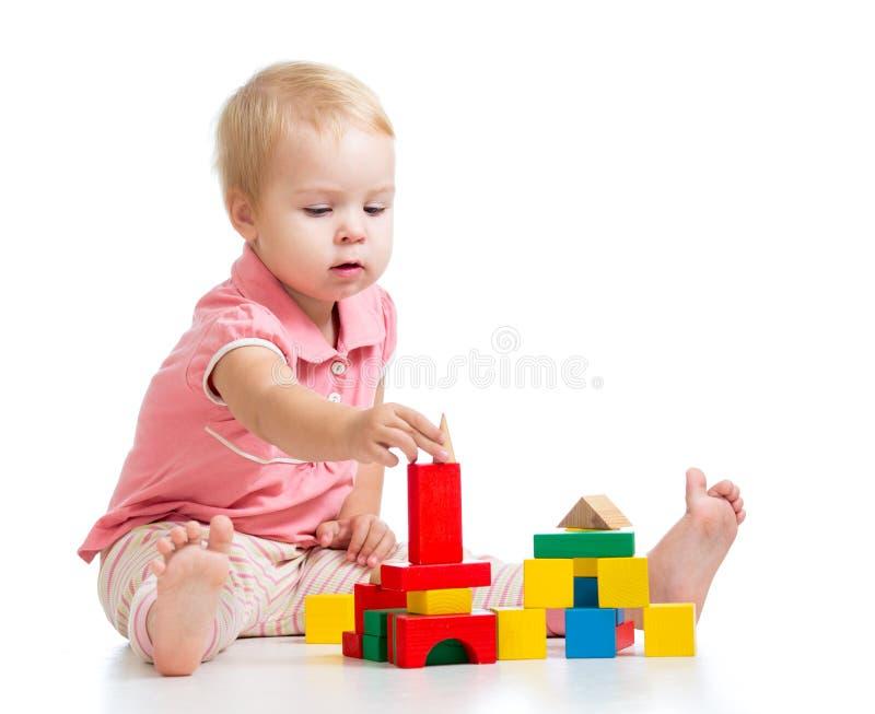 Menina do miúdo que joga blocos do brinquedo e que constrói a torre imagens de stock royalty free