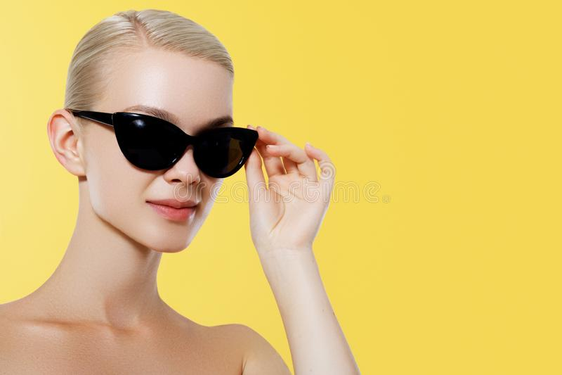 Menina do modelo de forma isolada sobre o fundo amarelo Mulher loura à moda da beleza que levanta em óculos de sol pretos retros  imagens de stock royalty free