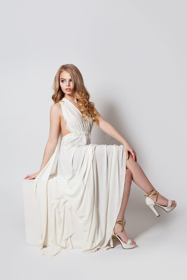 Menina do modelo de forma no vestido e nos pés brancos em sapatas dos saltos altos no fundo branco fotos de stock royalty free