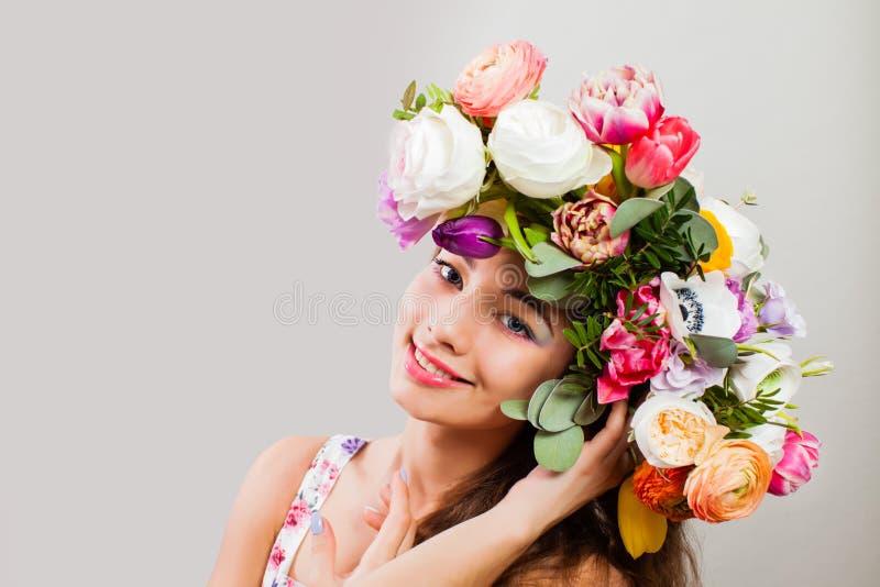 A menina do modelo do verão da beleza com flores coloridas envolve e forma a composição imagens de stock royalty free