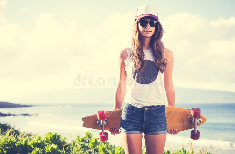 Menina do moderno com os óculos de sol vestindo da placa do patim imagens de stock
