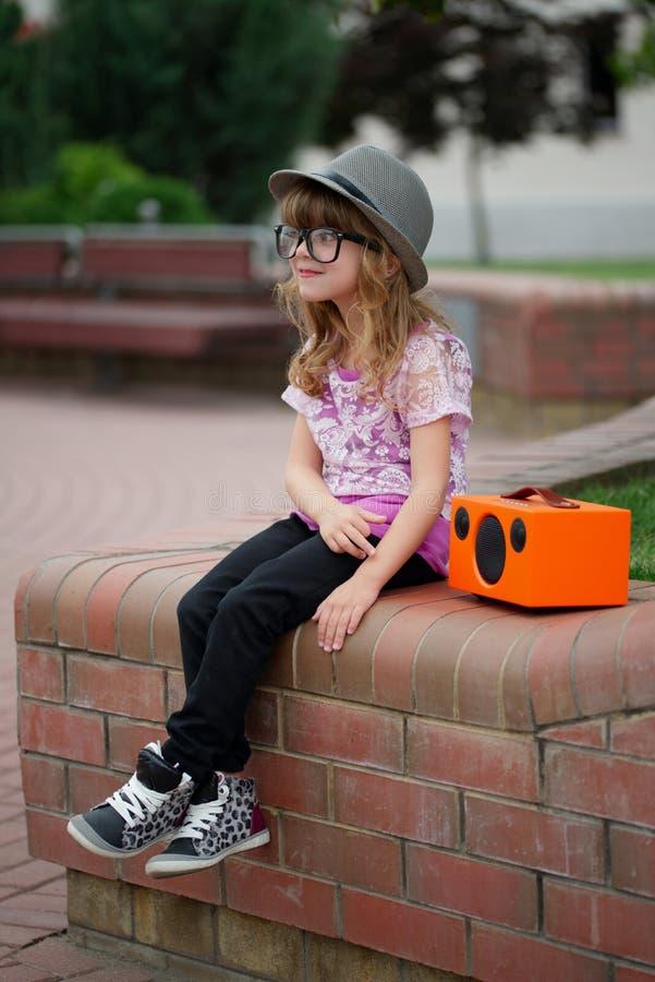 A menina do moderno escuta música no orador de vista retro sem fio imagens de stock royalty free