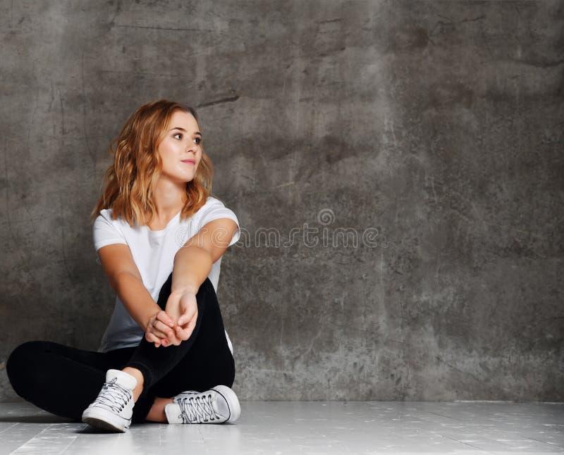 Menina do moderno que veste o t-shirt branco vazio, calças de brim contra a parede, imagem de stock royalty free